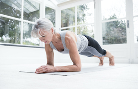 Senior woman in plank position in conservatory